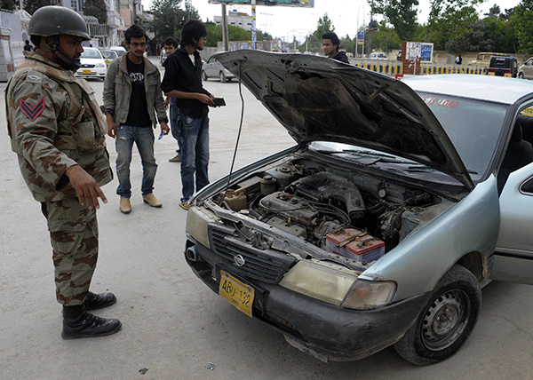 A paramilitary official searches a car at a checkpoint in Balochistan. Banaras Khan—AFP