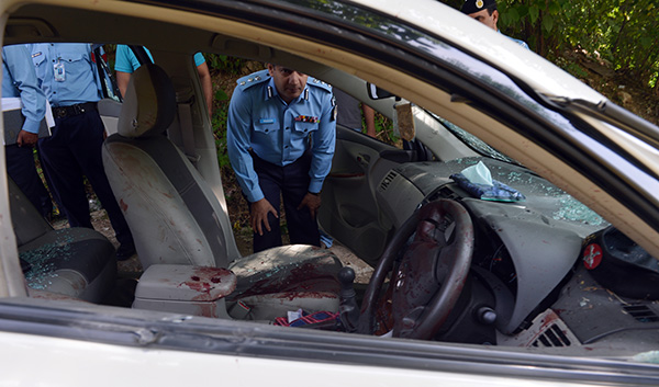 Police examine Chaudhry Zulfiqar's vehicle after he was shot by unidentified gunmen. Aamir Qureshi—AFP