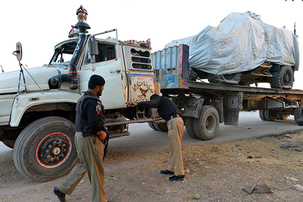 Pakistani police examine a NATO tanker torched by militants. A. Majeed—AFP