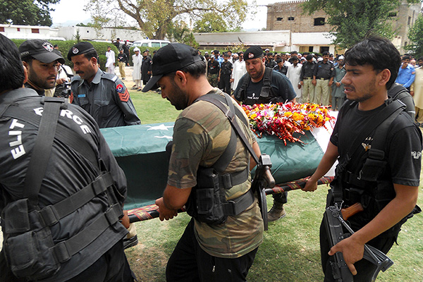 Policemen carry the coffin of a colleague killed in last night's ambush. Basit Shah—AFP