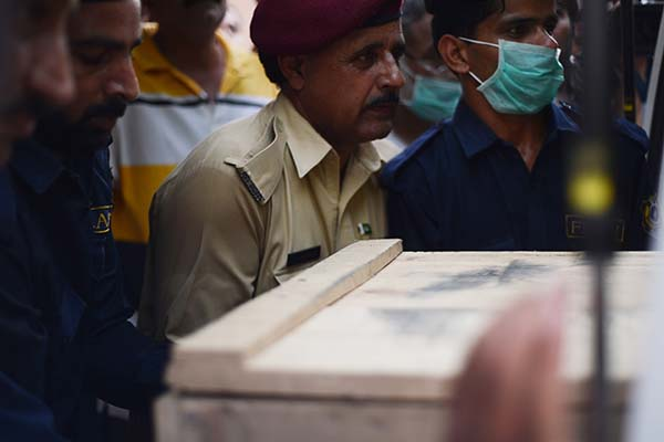 Rescuers transfer coffins from ambulances to an Islamabad hospital. Farooq Naeem—AFP