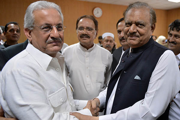 Presidential candidates Mamnoon Hussain (right) and Raza Rabbani shake hands after submitting their nomination papers. Aamir Qureshi—AFP