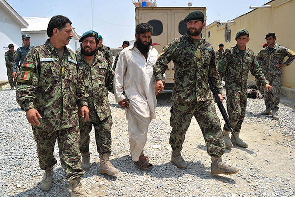Afghan soldiers escort a captured Taliban fighter in Jalalabad. Noorullah Shirzada—AFP