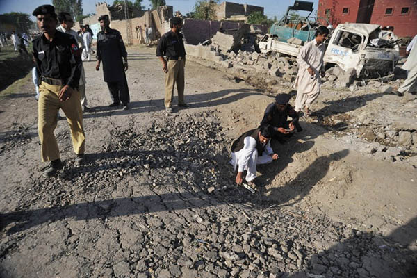 Investigators collect evidence at the site of a blast in Charsadda, 2011. A. Majeed—AFP