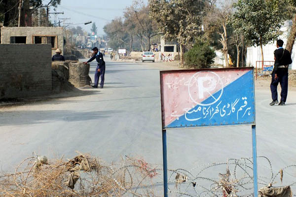 Police stand guard at a checkpost near the site of the Bannu bombing. Karim Ullah—AFP