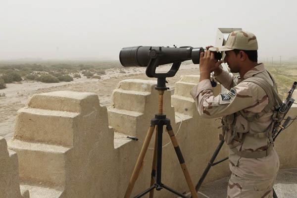An Iranian border guard examines his jurisdiction, July 2011. Atta Kenare—AFP