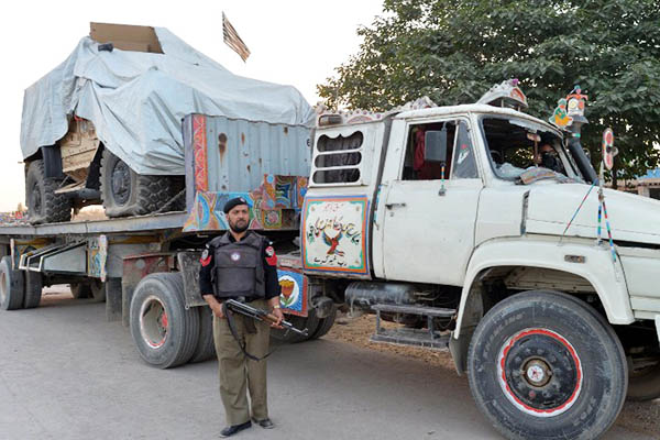 A policeman stands guard next to a truck transporting goods for NATO, May 2013. A. Majeed—AFP