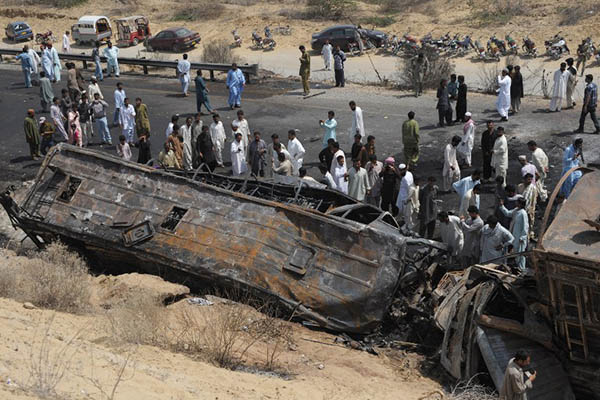 Onlookers gather at the site of a bus crash in Balochistan, March 2014. Rizwan Tabassum—AFP