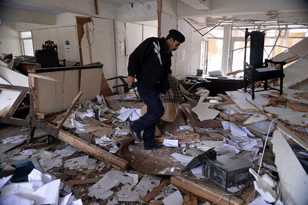 A police officer inspects the Islamabad district courts a day after 11 people were killed in a twin suicide bombing. Aamir Qureshi—AFP