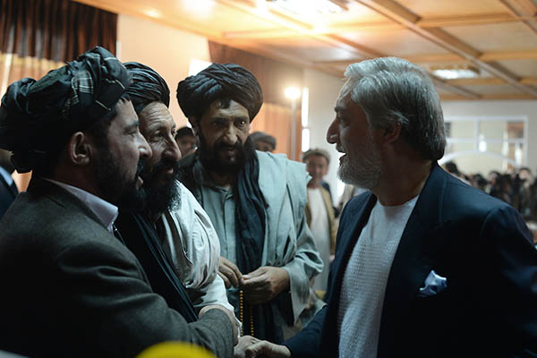 Abdullah Abdullah (right) shakes hands with his supporters. Shah Marai—AFP