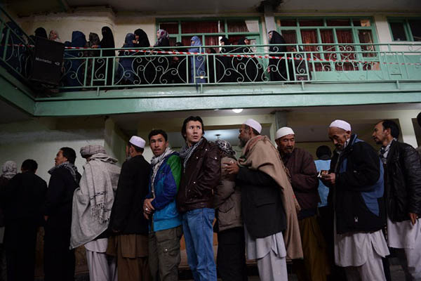 Afghan men and women wait to vote at a polling station in Kabul. Shah Marai—AFP