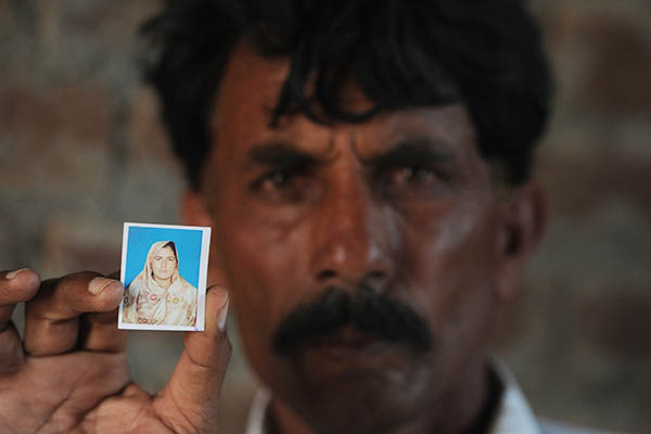 Mohammad Iqbal holds a picture of his wife, Farzana. Aamir Qureshi—AFP