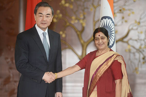 Chinese Foreign Affairs Minister Wang Yi shakes hands with Indian Minister for External Affairs Sushma Swaraj in New Delhi, June 2014. Raveendran—AFP