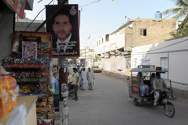 A poster of a Shia victim of a car bombing hangs outside a shop in Abbas Town. Rizwan Tabassum—AFP