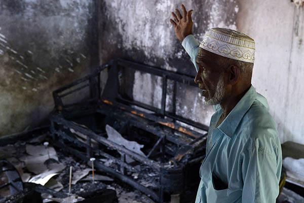 A Sri Lankan Muslim gestures toward his charred home in Aluthgama. Lakruwan Wanniarachchi—AFP