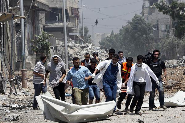 Medics evacuate a body from an embattled Gaza district. Mahmud Hams—AFP