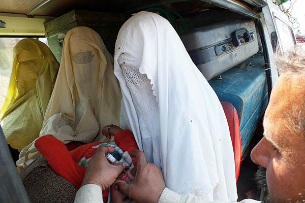 Health workers administer polio vaccinations to IDPs fleeing the North Waziristan military operation. Karim Ullah—AFP