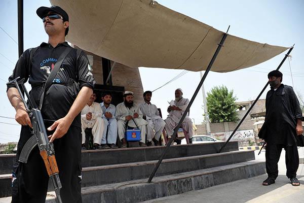 A police commando guards a polio vaccination team. Hasham Ahmed—AFP