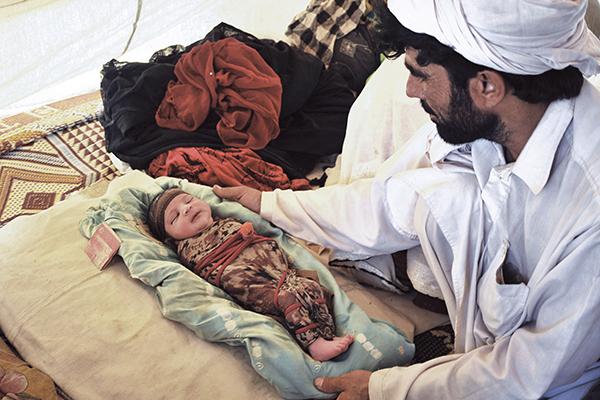Azb, born at Bakkakhel camp on June 28, with his father. Hasham Ahmed—AFP