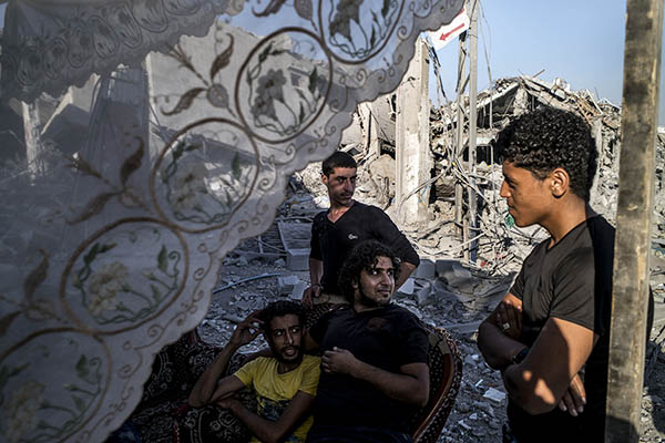 Palestinians stand at a makeshift shelter outside their destroyed home. Marco Longari—AFP