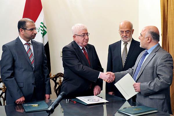 Iraqi President Fuad Masum (left) shakes hands with newly nominated prime minister Haidar al-Abadi. Iraqi President Office-HO—AFP