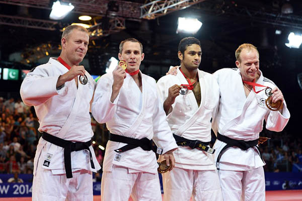 Shah Hussain (2nd right) displays his silver medal at the Commonwealth Games. Carl Court—AFP