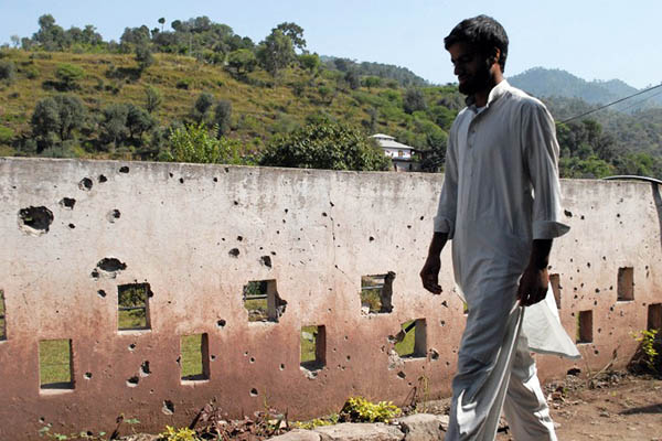 A resident of Pakistan-administered Kashmir walks past a shrapnel-marked wall. Sajjad Qayyum—AFP