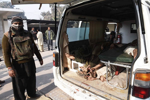 A security official stands next to bodies of suspected Taliban militants. A. Majeed—AFP