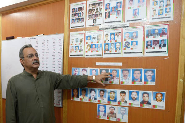 Senior MQM leader Haider Abbas Rizvi shows pictures of party activists believed to have been targeted in extra-judicial executions. Rizwan Tabassum—AFP