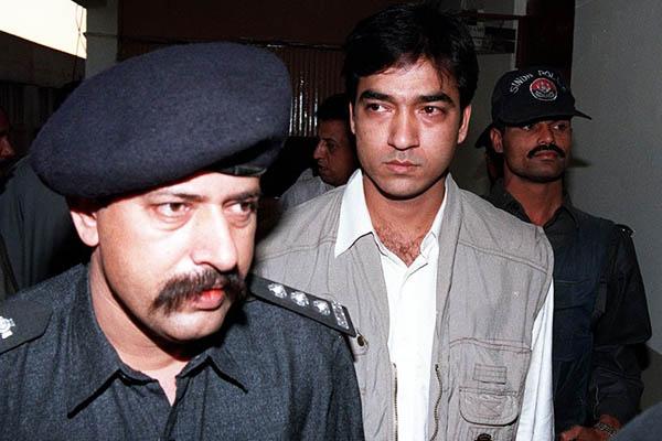 Saulat Mirza escorted by police in Karachi, 1998. Aamir Qureshi—AFP