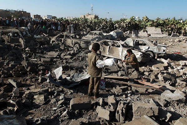 Yemenis examine the site of a Saudi airstrike targeting Houthi rebels near Sanaa Airport on March 26. Mohammed Huwais—AFP