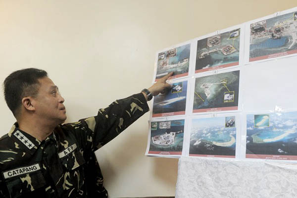 Filipino military chief Gen. Gregorio Catapang points to aerial photos of Chinese construction over reefs and shoals in the Spratly archipelago. Jay Directo—AFP