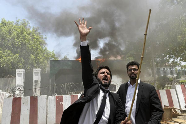 Lawyers set fire to the checkpoint entrance of the Punjab Assembly in Lahore, May 26, 2015. Arif Ali—AFP