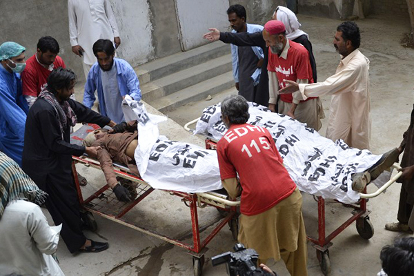 Volunteers move the bodies of two welders gunned down in Quetta, July 1. Banaras Khan—AFP