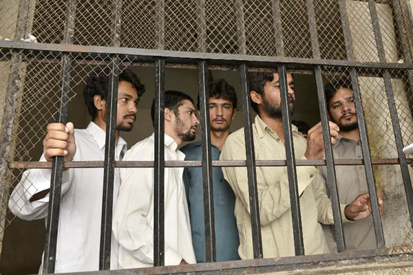 Arrested members of a gang that allegedly abused and blackmailed hundreds of children. Arif Ali—AFP
