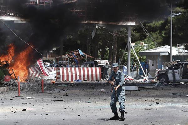 An Afghan policeman outside the site of a huge blast in Kabul. Shah Marai—AFP