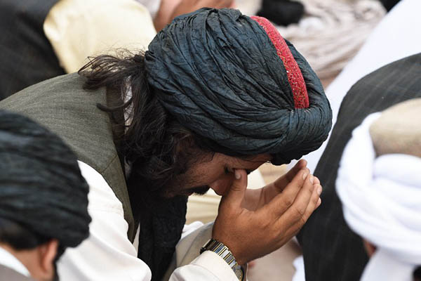 Mourners in Pakistan pray for Taliban chief Mullah Omar after his death. Banaras Khan—AFP