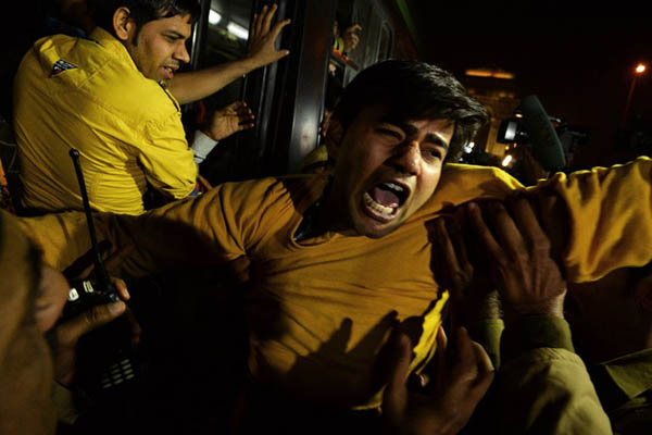 Demonstrators shout slogans after being taken into custody by police officials. Chandan Khanna—AFP