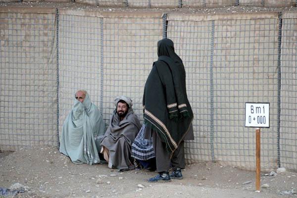 Afghan men wait near the Kandahar airport. Jawed Tanveer—AFP