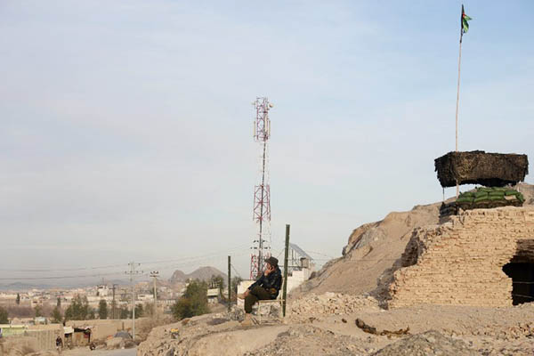 An Afghan policeman sits near a private cellphone antenna. Jawed Tanveer—AFP