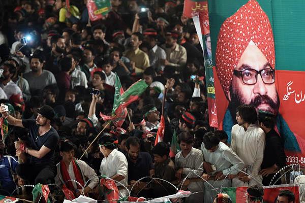 PTI activists gather in front of a poster featuring Sardar Soran Singh. Farooq Naeem—AFP