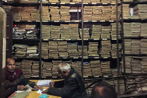 Indian government employees work next to stacks of files at the office of the registrar in the district court of Allahabad. Chandan Khanna—AFP